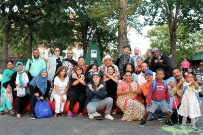 The event organizers and participating organizations and local businesses band together for a group photo crossing their arms in a proud X for the Bronx.