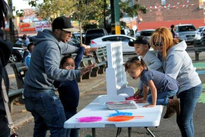 Parents and children enjoy a lively game of giant Connect Four.